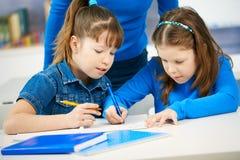 Colegialas que aprenden en sala de clase Imágenes de archivo libres de regalías