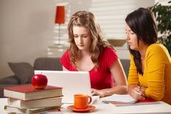 Colegialas que estudian en la tabla. Fotos de archivo