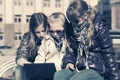 Colegialas que usan el ordenador portátil en el banco Foto de archivo libre de regalías