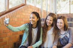 Colegialas sonrientes que se sientan en la escalera que toma el selfie con el teléfono móvil Fotos de archivo
