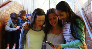 Colegialas sonrientes que toman el selfie con el teléfono móvil en pasillo almacen de metraje de vídeo