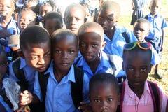 Colegialas y muchachos haitianos jovenes en curiosamente la actitud para la cámara en pueblo rural Foto de archivo