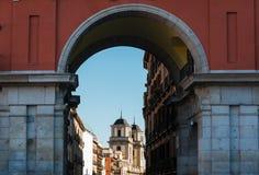 Colegiata de San Isidro from the Plaza Mayor. Colegiata de San Isidro church as seen through the arches of the Plaza Mayor in Madrid, Spain Royalty Free Stock Photo