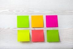 Coleção da nota colorida do papel do post-it no fundo de madeira branco Fotografia de Stock Royalty Free