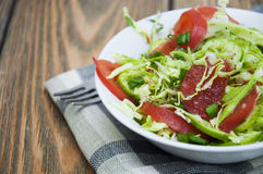 Coleslaw. Salad with fresh cabbage, tomato, cucumber and herbs on the plate on a table Stock Photos