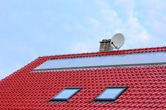 Coletores solares lisos em um telhado vermelho Imagens de Stock Royalty Free