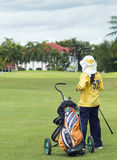 Colf caddie on the fairway. Golf caddie and bag on the fairway, admiring a luxury house on the outskirt of the golf course. The villa in the background out of Royalty Free Stock Photo