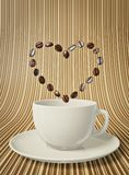 Colffee. Heart of coffee beans on a white cup Royalty Free Stock Photos