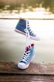 Colgante atado de las zapatillas de deporte del par de tejanos Fotos de archivo
