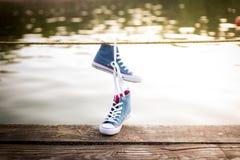 Colgante atado de las zapatillas de deporte del par de tejanos Fotografía de archivo libre de regalías