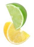 Colgante, cayendo, volando cortando el pedazo de frutas del limón y de la cal aisladas en blanco con la trayectoria de recortes Foto de archivo