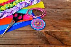 Colgante colorido del fieltro - joyería hecha a mano Hágalo usted mismo Tijeras, hojas del fieltro en un fondo de madera con el e Foto de archivo libre de regalías
