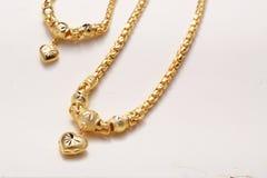Colgante de oro del corazón, cordón del cuello, pulsera de oro Imágenes de archivo libres de regalías