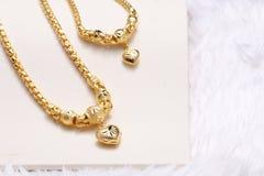 Colgante de oro del corazón, cordón del cuello, pulsera de oro Fotos de archivo