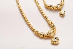 Colgante de oro del corazón, cordón del cuello, pulsera de oro Fotografía de archivo libre de regalías