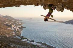 Colgante femenino del escalador de roca al revés en la ruta estimulante en cueva en la puesta del sol fotografía de archivo