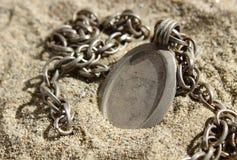 Colgante rústico y cadena enterrados en arena Fotos de archivo