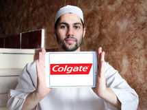 Colgate logo. Logo of toothpaste brand Colgate on samsung tablet holded by arab muslim man stock image