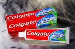 Colgate triplica o dentífrico da ação isolado no fundo do metal Imagem de Stock Royalty Free