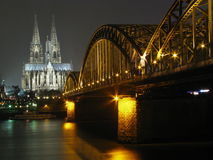 Colgne (Germany) cathedral by night. Cologne (Germany) cathedral and the Rhine bridge by night seen from the other bank of the river Stock Photography