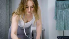 Colha a jovem mulher que dobra-se sobre esboços da roupa do desenho da tabela na oficina vídeos de arquivo