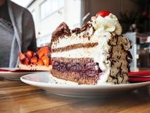 Colha a mulher que come o café com a Floresta Negra alemão do bolo da sobremesa imagens de stock