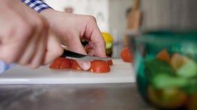 Colha o homem irreconhecível que está na tabela na cozinha e que desbasta o tomate na placa de corte video estoque