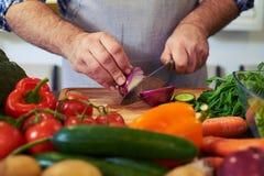 Colha o tiro das mãos que cortam uma cebola com uma faca Fotografia de Stock Royalty Free