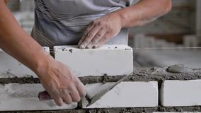Colha o trabalhador irreconhecível que coloca tijolos ao trabalhar no canteiro de obras filme