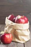Colheita das maçãs em um pacote de papel em um fundo de madeira escuro Fotos de Stock Royalty Free