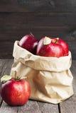 Colheita das maçãs em um pacote de papel em um fundo de madeira escuro Fotografia de Stock