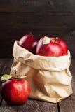 Colheita das maçãs em um pacote de papel em um fundo de madeira escuro Imagem de Stock Royalty Free