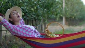 A colheita do fruto, menina do fazendeiro aprecia relaxar na rede e comer maçãs da cesta video estoque