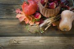 Colheita do outono, abóbora, maçãs na cesta, folhas de outono coloridas na placa de madeira Copie o espaço Vista superior Imagens de Stock