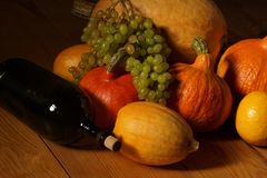 Colheita do outono das abóboras e das uvas, e uma garrafa do vinho Imagens de Stock