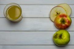 Colheita do todo e do corte das maçãs do outono e suco de maçã maduros vermelhos e verdes, de cima na tabela de madeira branca Imagens de Stock Royalty Free