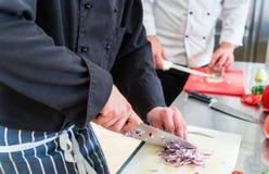 Colheita dos cozinheiros chefe que cortam cebolas e outros ingredientes de alimento Imagem de Stock Royalty Free