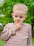 Colheita ereta do rapaz pequeno seu nariz foto de stock royalty free