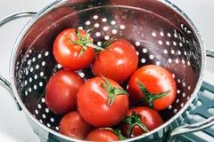 Colheita fresca dos tomates lavada em um escorredor Fotografia de Stock