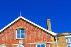 Colheita próxima de uma casa do tijolo vermelho contra um céu sem nuvens imagens de stock