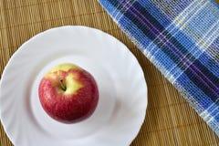 A colheita vermelha do outono das maçãs encontra-se em uma placa branca Imagens de Stock Royalty Free