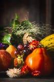 Colhendo frutas e legumes na mesa de cozinha rústica escura no fundo de madeira, vista lateral Imagens de Stock Royalty Free
