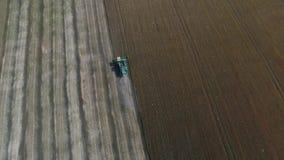 Colhendo o campo de trigo com maquinaria agrícola Fotografia aérea com um zangão video estoque