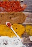 Colher branca com açafrão perto das especiarias coloridas diferentes no fundo de madeira Imagem de Stock Royalty Free
