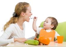 Colher brincalhão do bebê que alimenta sua matriz foto de stock royalty free