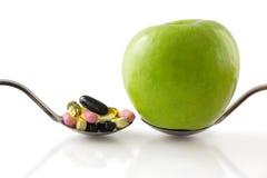 Colher com a maçã contra a colher com comprimidos. Fotos de Stock