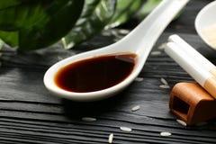 Colher com molho de soja saboroso na tabela de madeira, fotografia de stock