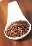 Colher com o chá vermelho frouxo de Rooibos isolado imagens de stock royalty free