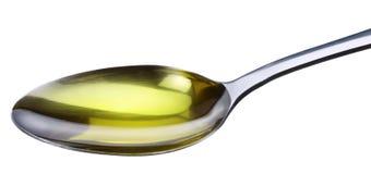 Colher com petróleo verde-oliva. Imagens de Stock