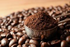 Colher com terras de café e os feijões roasted na tabela imagem de stock royalty free